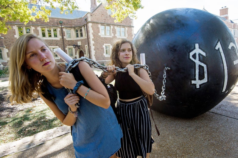 Two young women hold a chain connected to a gigantic black ball with $1.4 trillion written on it.