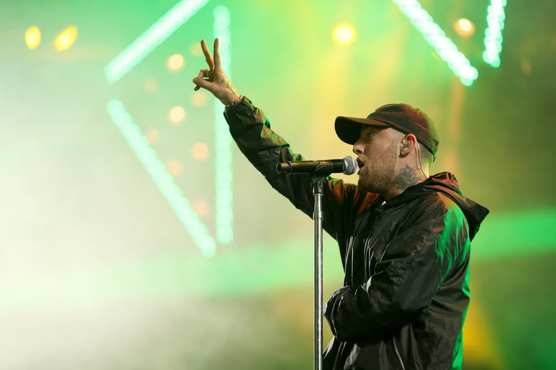 Mac Miller stands onstage at a microphone, holding up two fingers.