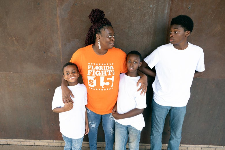Monica smiles and stands with her three sons, with her arms around two of them
