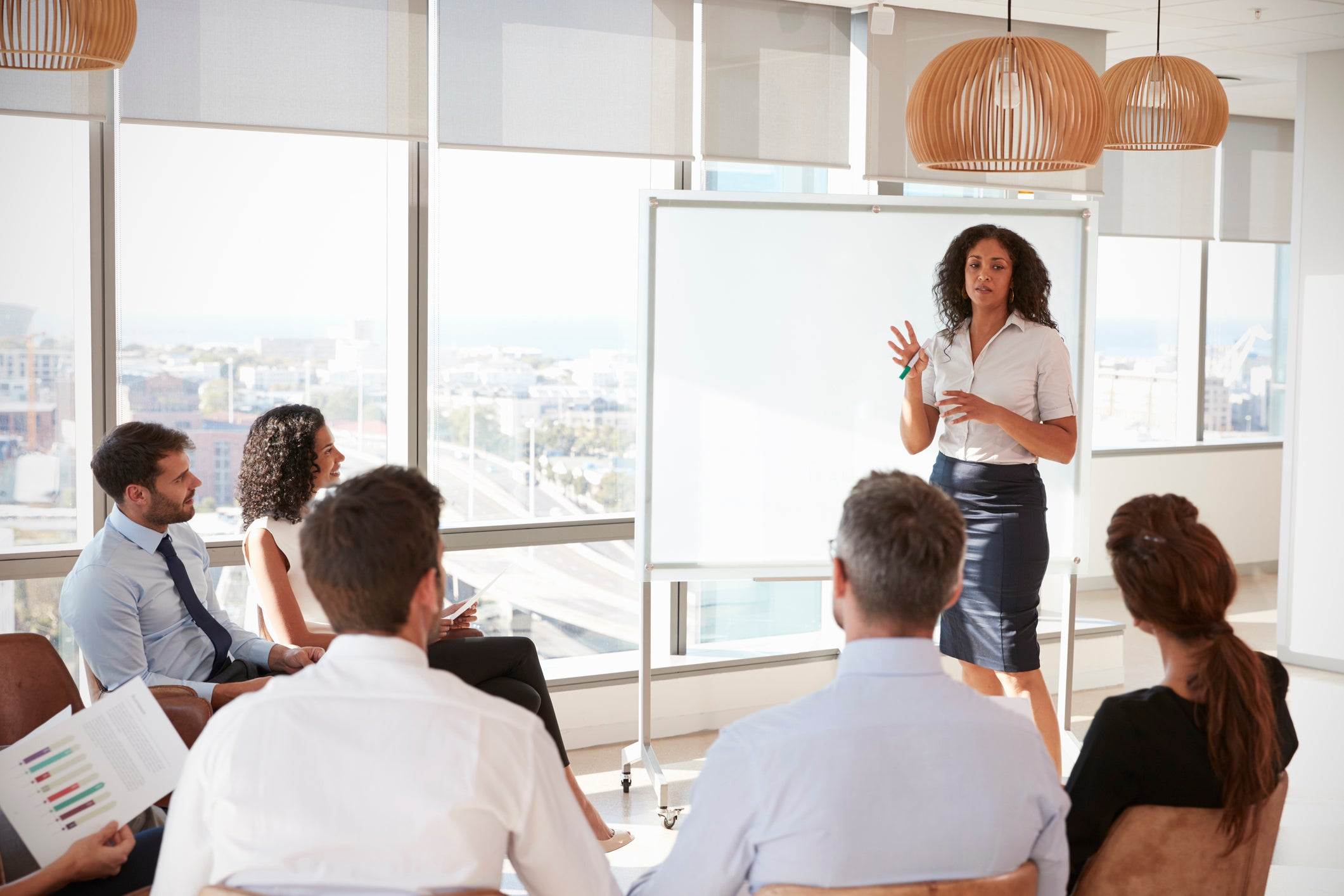 A businesswoman presents to a room of colleagues.