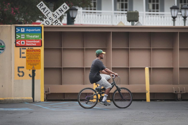 NEW ORLEANS, LOUISIANA - JULY 12: A cyclist rides past a flood gate that has been closed to keep the Mississippi River from inundating the French Quarter with storm surge from Hurricane Barry on July 12, 2019 in New Orleans, Louisiana. The slow moving storm is expected to make landfall as a tropical storm or weak hurricane near Morgan City, Louisiana. Flash flood watches have been issued over much of of Louisiana and Mississippi as the storm is expected to dump more than a foot of rain in many areas and up to 25 inches in some isolated locations.  (Photo by Scott Olson/Getty Images)