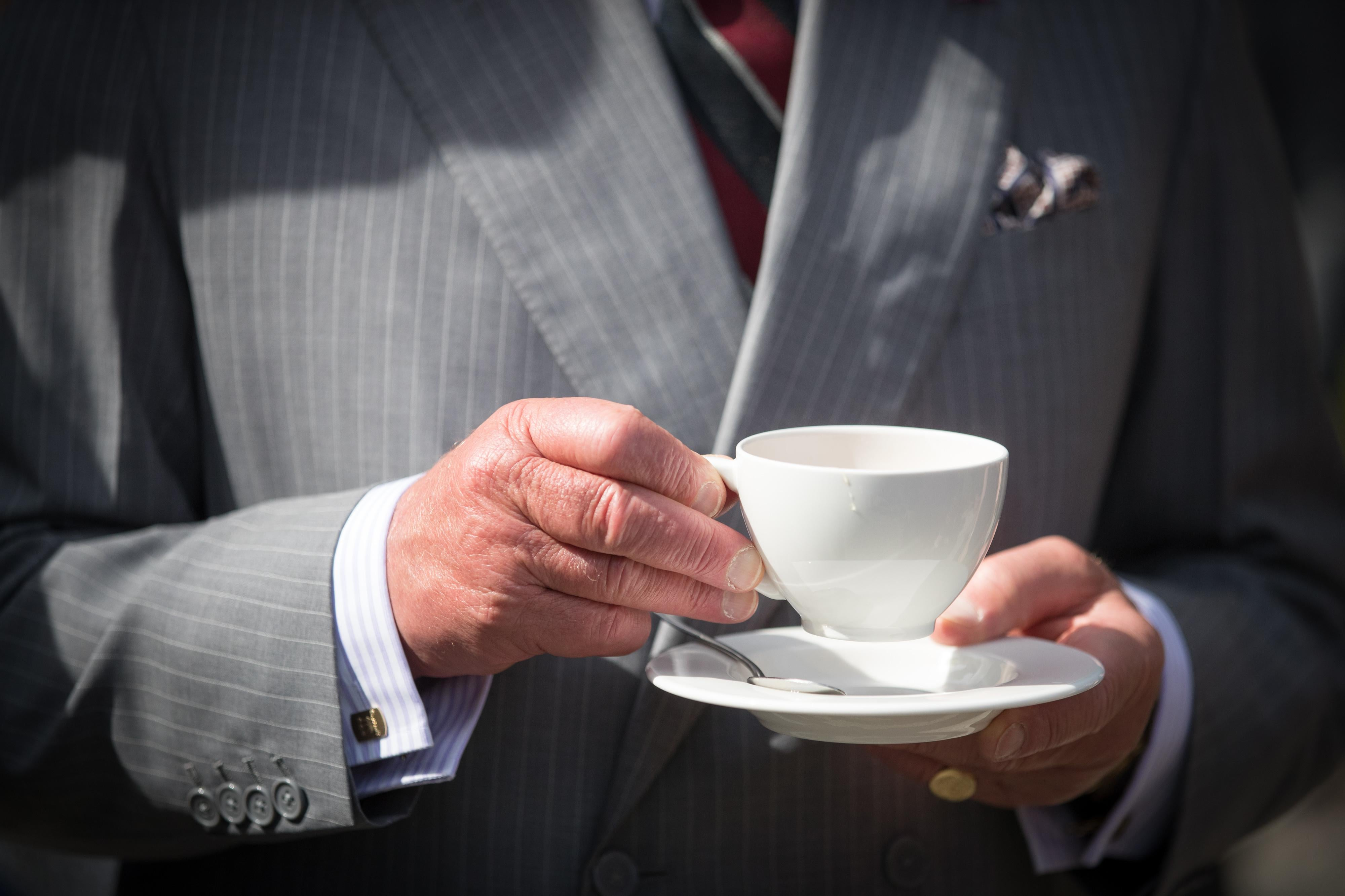 Prince Charles, Prince of Wales has a cup of tea as he takes a tour of the gardens at Plas Cadnant Hidden Gardens.