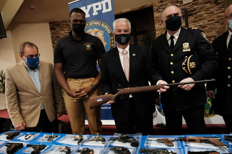 Law enforcement officials hold a rifle and stand over a table of handguns.