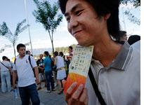 A Chinese man holds a ticket for sale outside the Olympic green. Click image to expand.