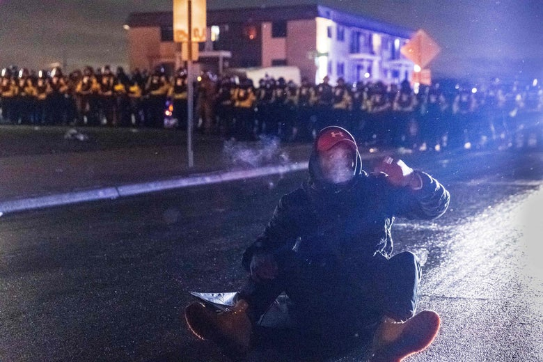 A person gestures while sitting on a road near the Brooklyn Center police station at night. Rows and rows of police loom in the background.