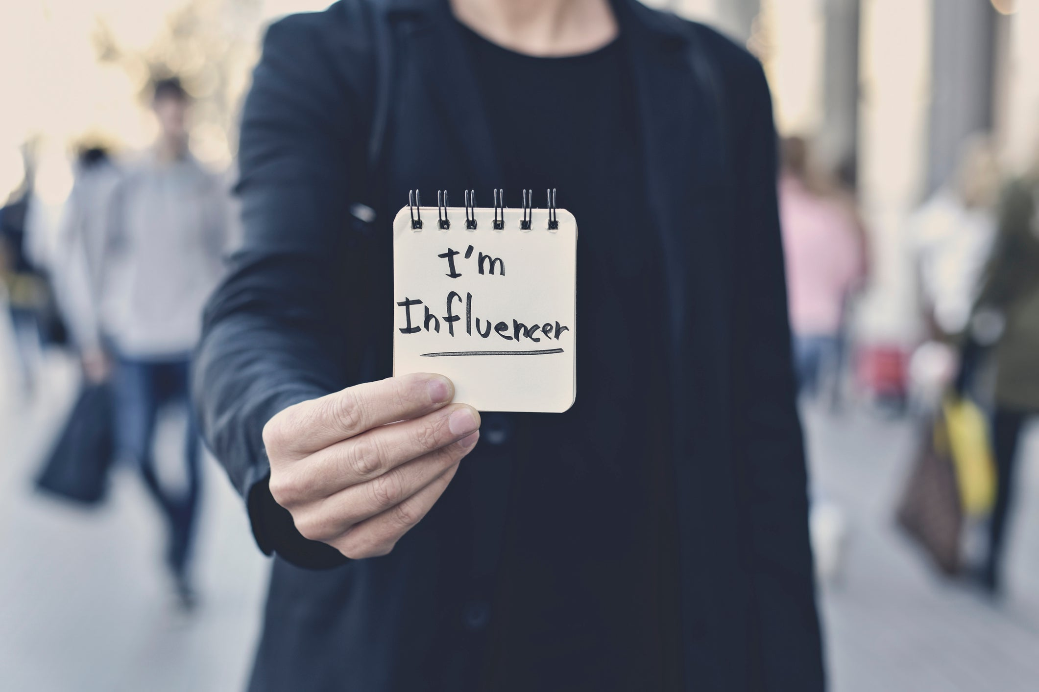 "A young Caucasian man holds a name tag that says, ""I am Influencer."""