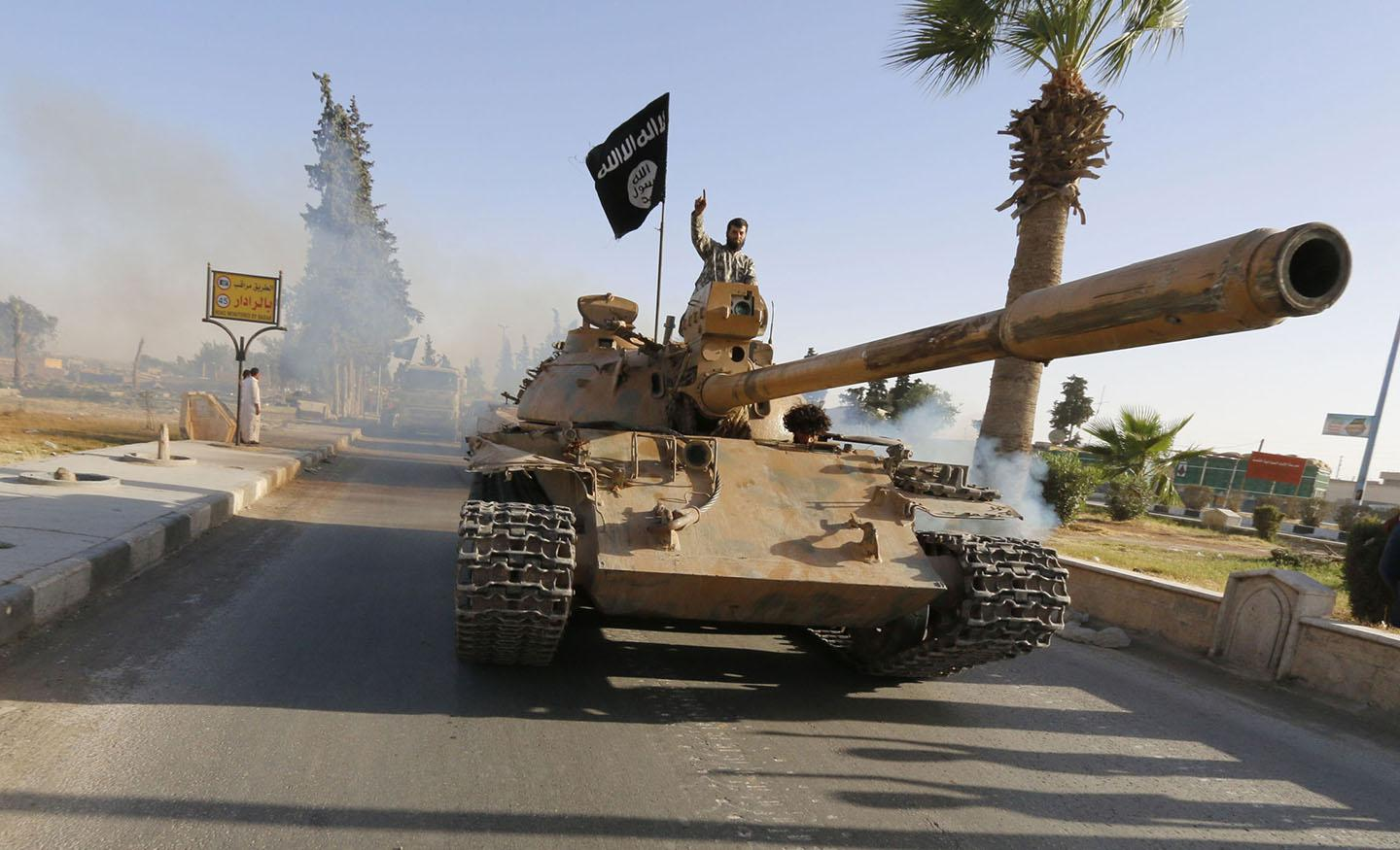 ISIS fighters on a tank take part in a military parade along the streets of northern Raqqa province June 30, 2014.