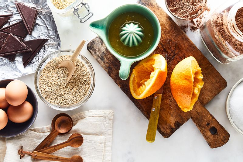 Ingredients and kitchen devices are artfully scattered around a counter: chocolate, eggs, quinoa, tablespoons, a juicer, juiced oranges, a cutting board, and cocoa powder can all be seen.