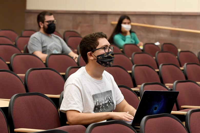Students wearing masks socially distance in a lecture hall