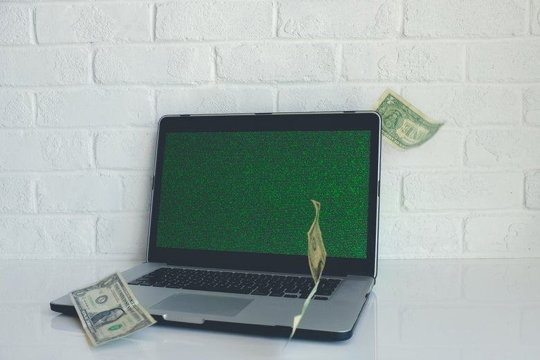 A laptop with green noise on the screen sits on a counter, with dollar bills floating around it.
