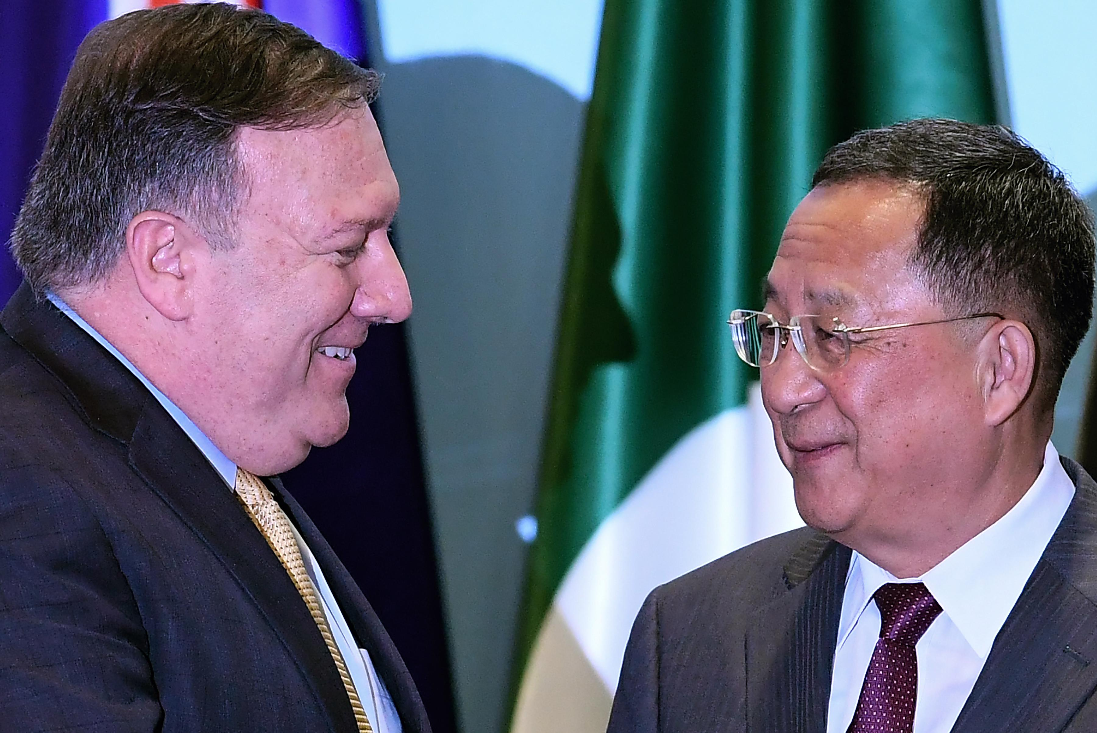 U.S. Secretary of State Mike Pompeo talks with North Korea's Foreign Minister Ri Yong Ho as they arrive for a group photo at the ASEAN Regional Forum in Singapore on August 4, 2018.
