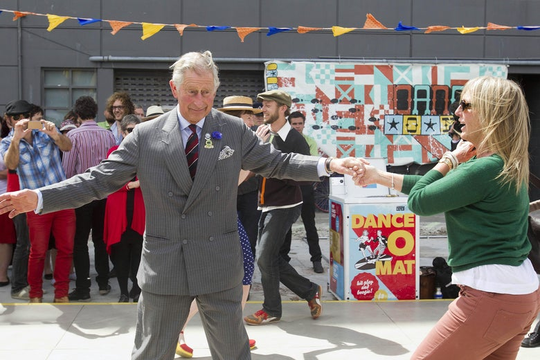 Prince Charles extends his arms while dancing in an empty lot turned civic space in Christchurch, with a crowd behind him