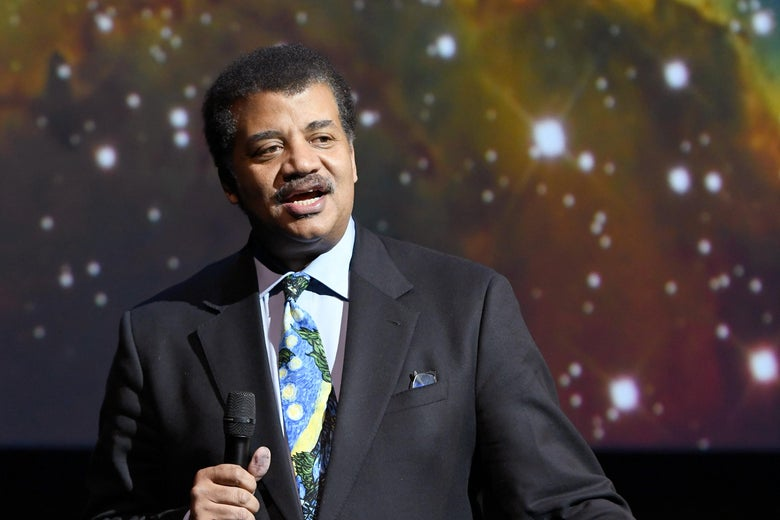 Neil deGrasse Tyson with an image of stars behind him.