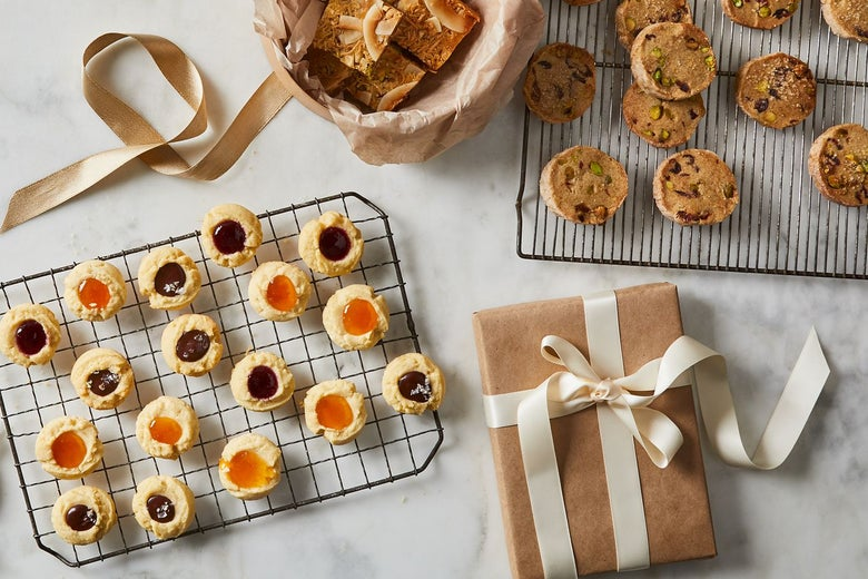 Cooling trays of thumbprint cookies and nut cookies next to a basket of bar cookies and a brown paper package tied up with ribbon