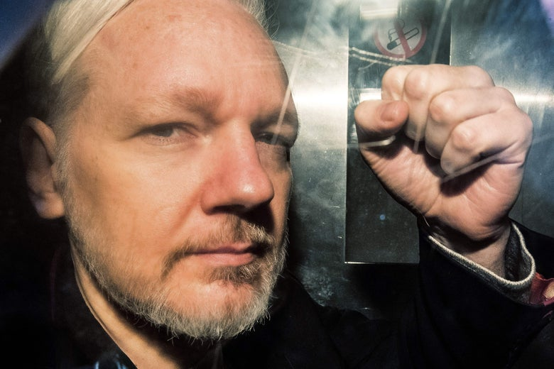Julian Assange, seen up close through a window, gestures with a hand in a fist.