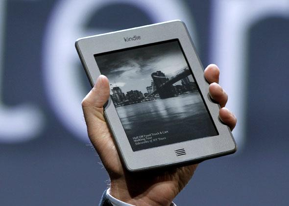 Amazon CEO Jeff Bezos holds up the new Kindle Touch at a news conference during the launch of Amazon's new tablets in New York September 28, 2011.