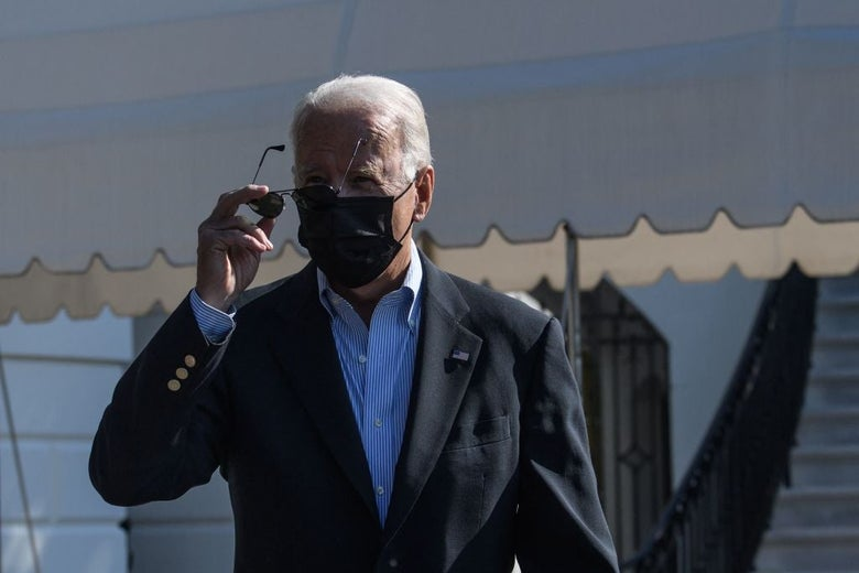 Biden, wearing a dark coat and blue shirt sans tie with a black mask, takes off a pair of aviator sunglasses.