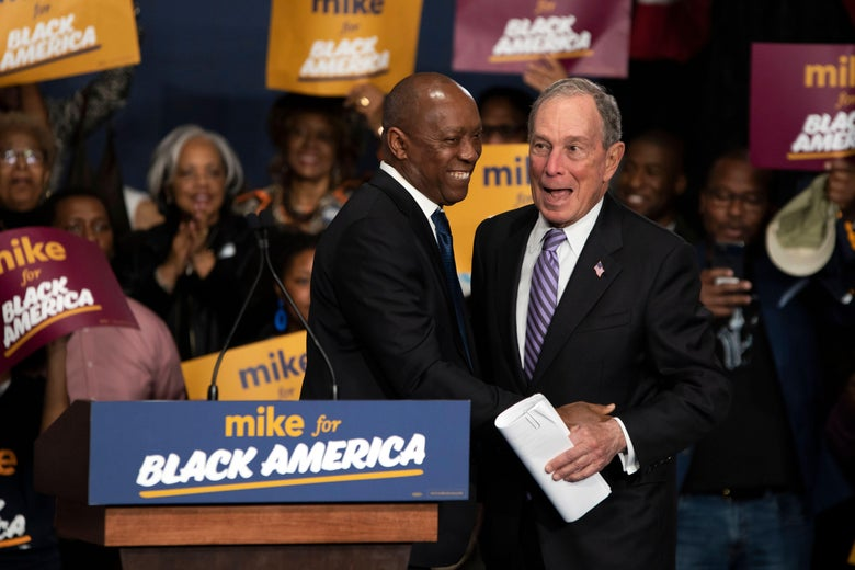 Mike Bloomberg receives a hug from a man onstage at a rally.