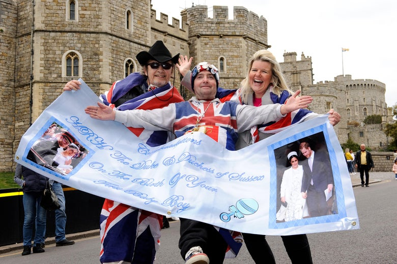 Three people dressed in Union Jack outfits carry a banner celebrating Prince Harry and Meghan's baby with Windsor Castle in the background.