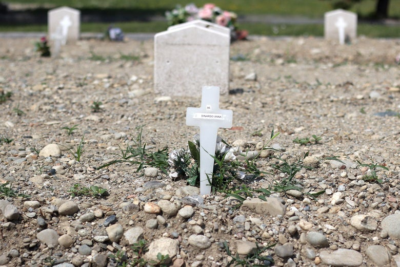 A close-up of a makeshift grave with a cross.