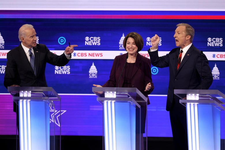 Joe Biden and Tom Steyer point angrily at each other as they speak on the debate stage. Amy Klobuchar, standing between them, smiles.