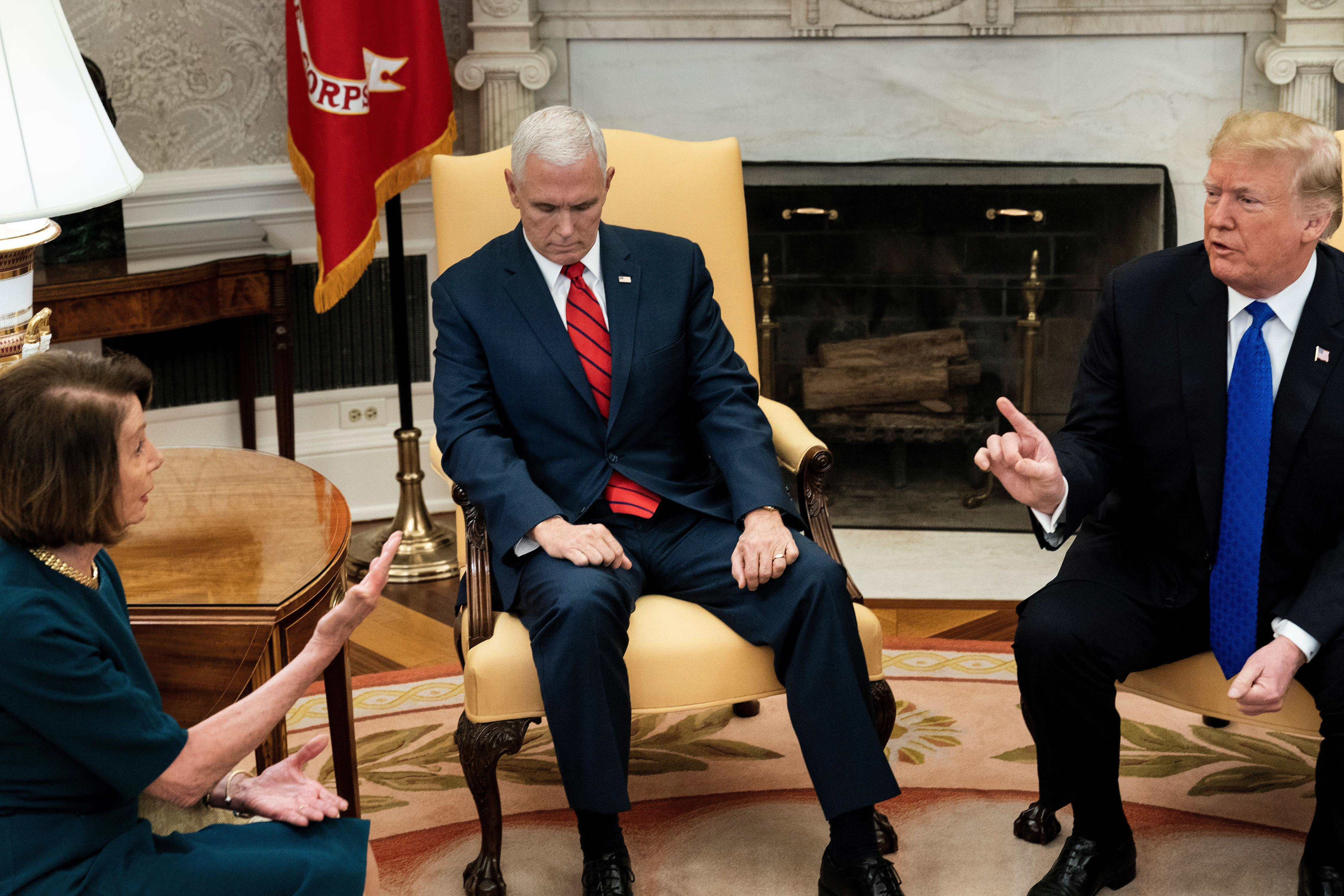 Mike Pence looks intently at his own hand as Nancy Pelosi and Donald Trump talk across him animatedly.