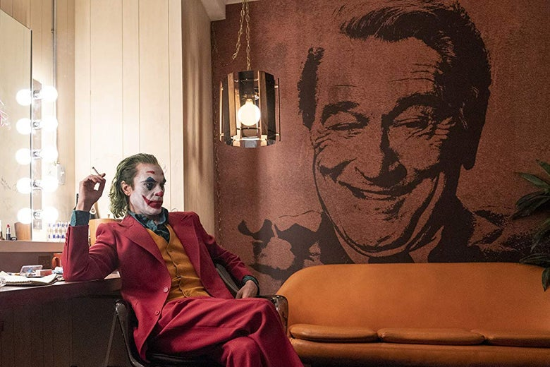 Joaquin Phoenix as the Joker has green hair and a face painted white, blue, and red. He sits holding a cigarette in front of a large mural of Robert de Niro's face.