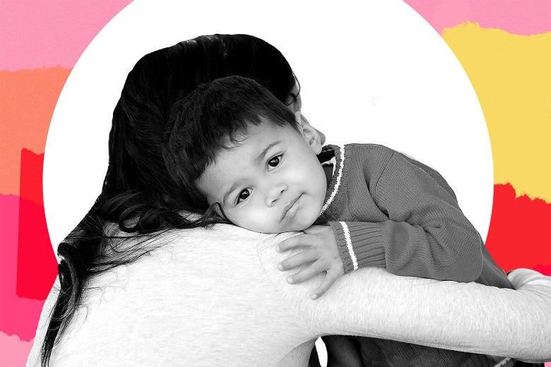 A Latina woman holding her young son over her shoulder.