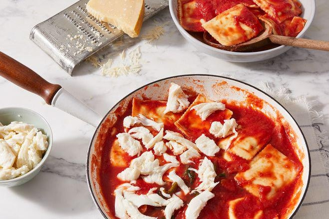 Ravioli in a skillet with tomato sauce and roughly torn pieces of mozzarella.