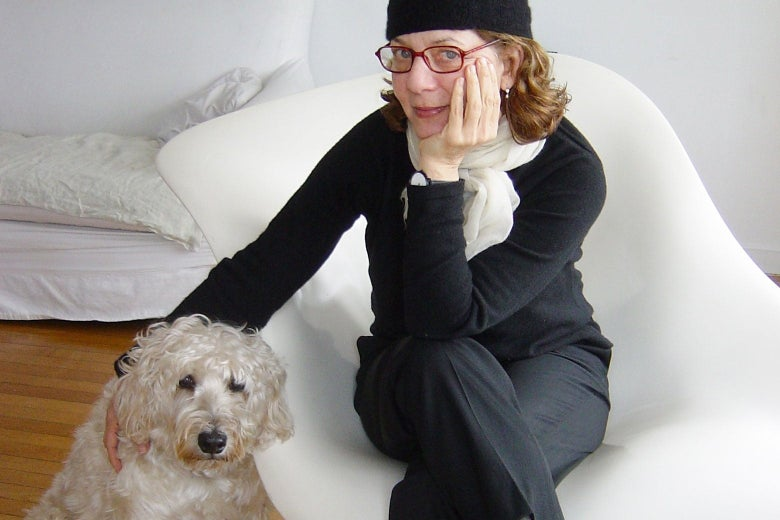 Maira Kalman sits on a white chair and puts her hand on her dog.