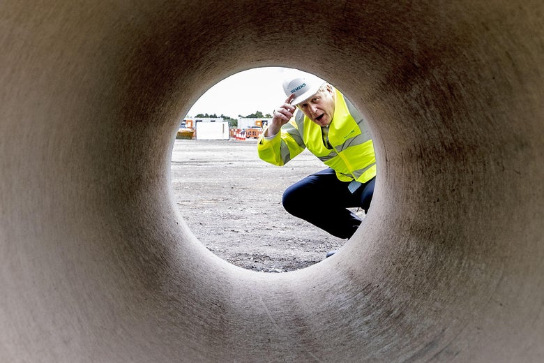 Boris Johnson kneels down to look through a large pipe.
