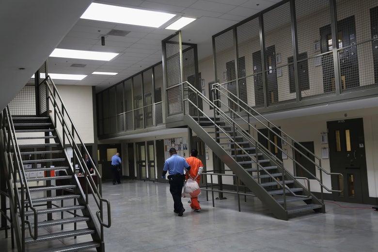 A guard pulls a handcuffed man in an orange jumpsuit.