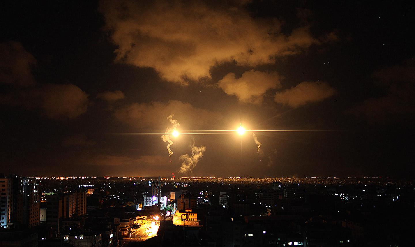 Aircraft flares illuminate the sky following an Israel airstrike over al-Suaciye district of Gaza City.