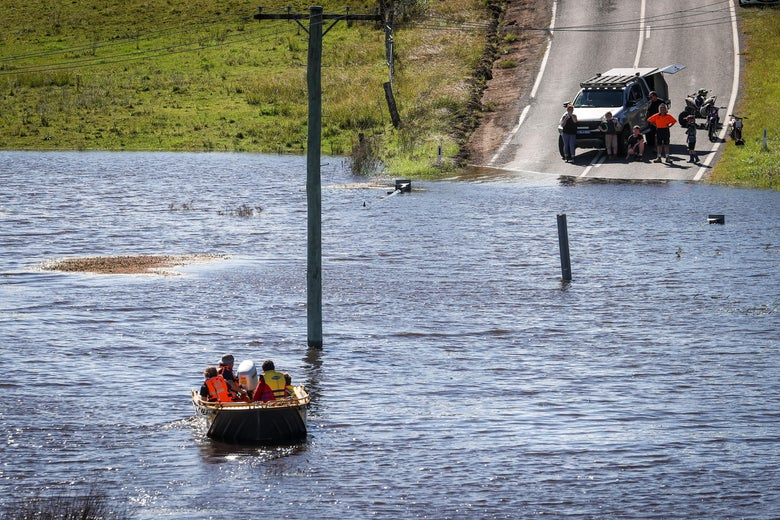 A boat filled with people crosses floodwaters towards a road.