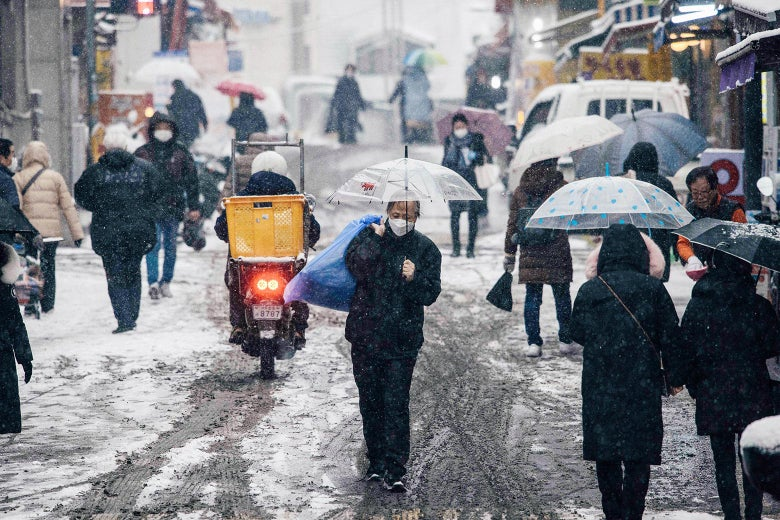 People walking in a street as it snows. Some are holding umbrellas and most are wearing masks, but it looks like just a regular day unaffected by the pandemic.