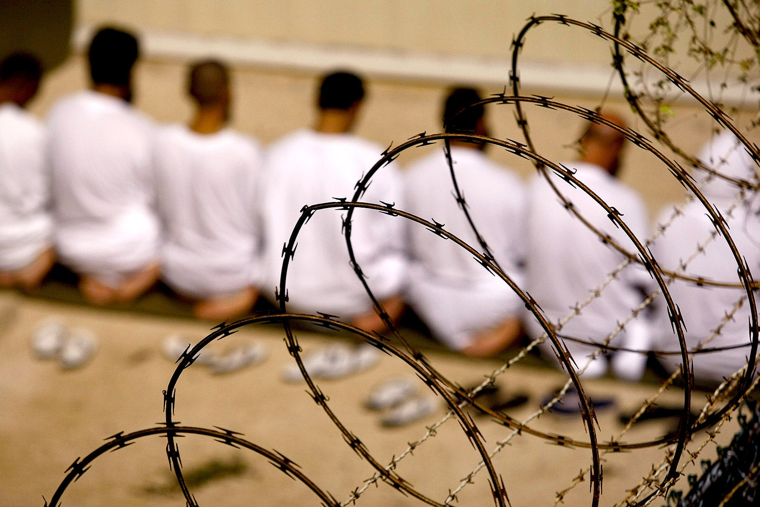 A group of detainees kneels during an early morning Islamic prayer in their camp in Guantanamo Bay, Cuba.