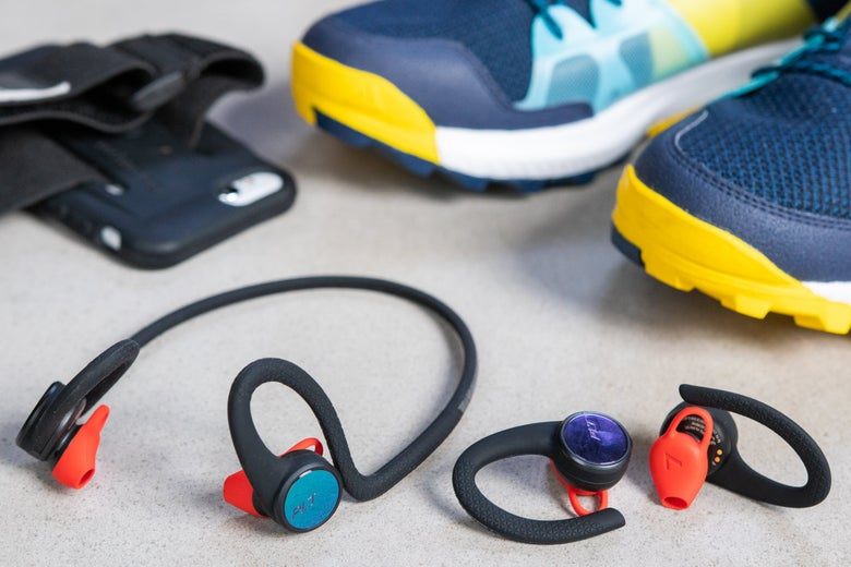 Two pairs of Plantronics headphones near a pair of sneakers.