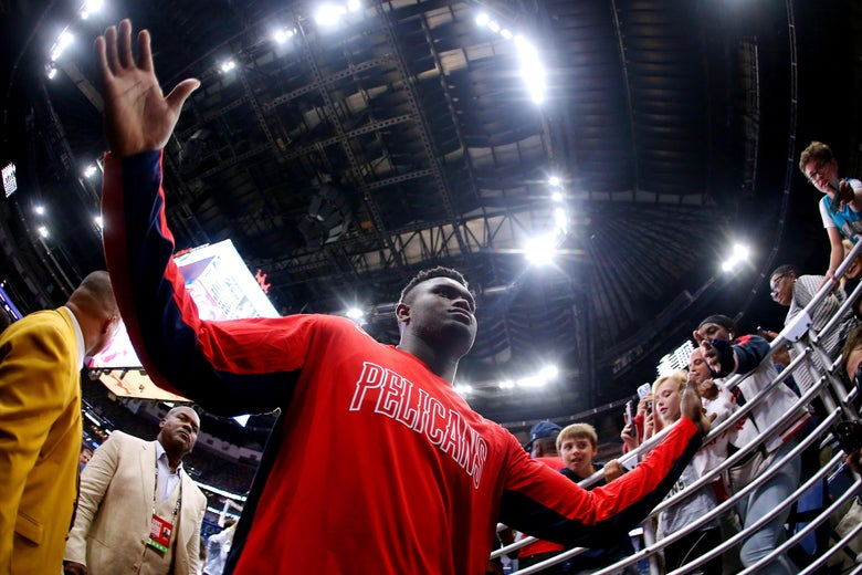Low-angle shot of Zion Williamson with arms raised as he walks off the court, with fans in the stands in the background.
