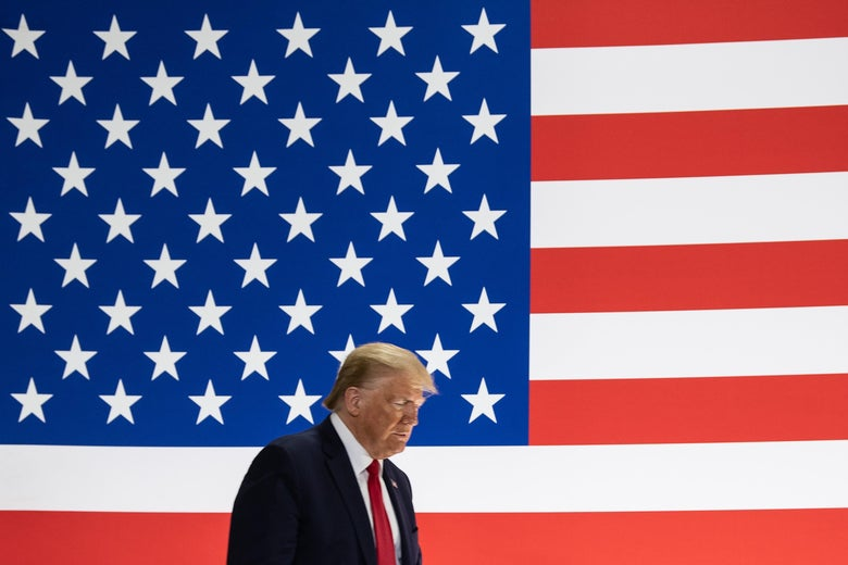 President Donald Trump walks in front of a giant American flag