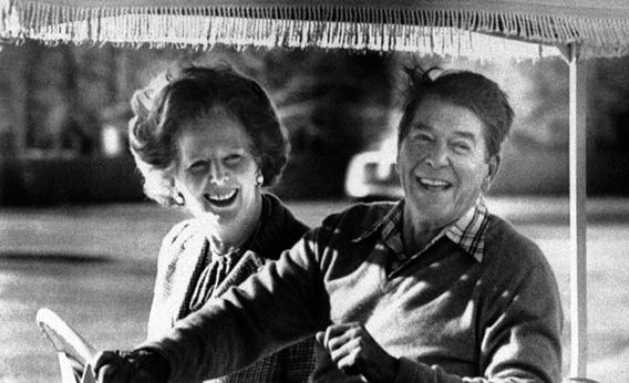 President Ronald Reagan and British Prime Minster Margaret Thatcher smile as they ride an electric cart at Camp David, Maryland on Dec. 22, 1984.