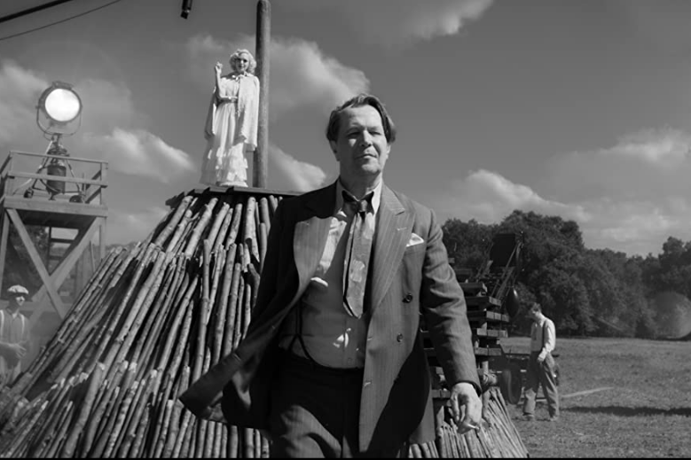 Gary Oldman strides away from Amanda Seyfried, who stands atop a wooden pyre.