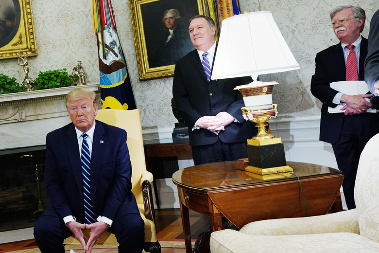 Trump seated, Pompeo and Bolton standing in the Oval Office.