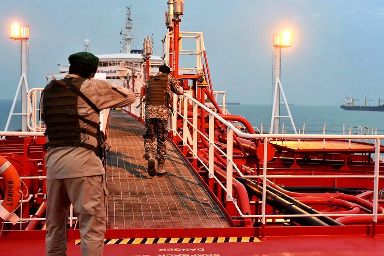 Two armed members of Iran's Revolutionary Guard inspect the British-flagged oil tanker Stena Impero.