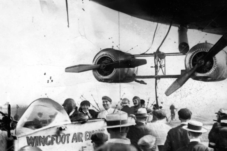 The open gondola of a 1910s blimp, flanked by two giant engines. Five smiling passengers sit in the gondola.