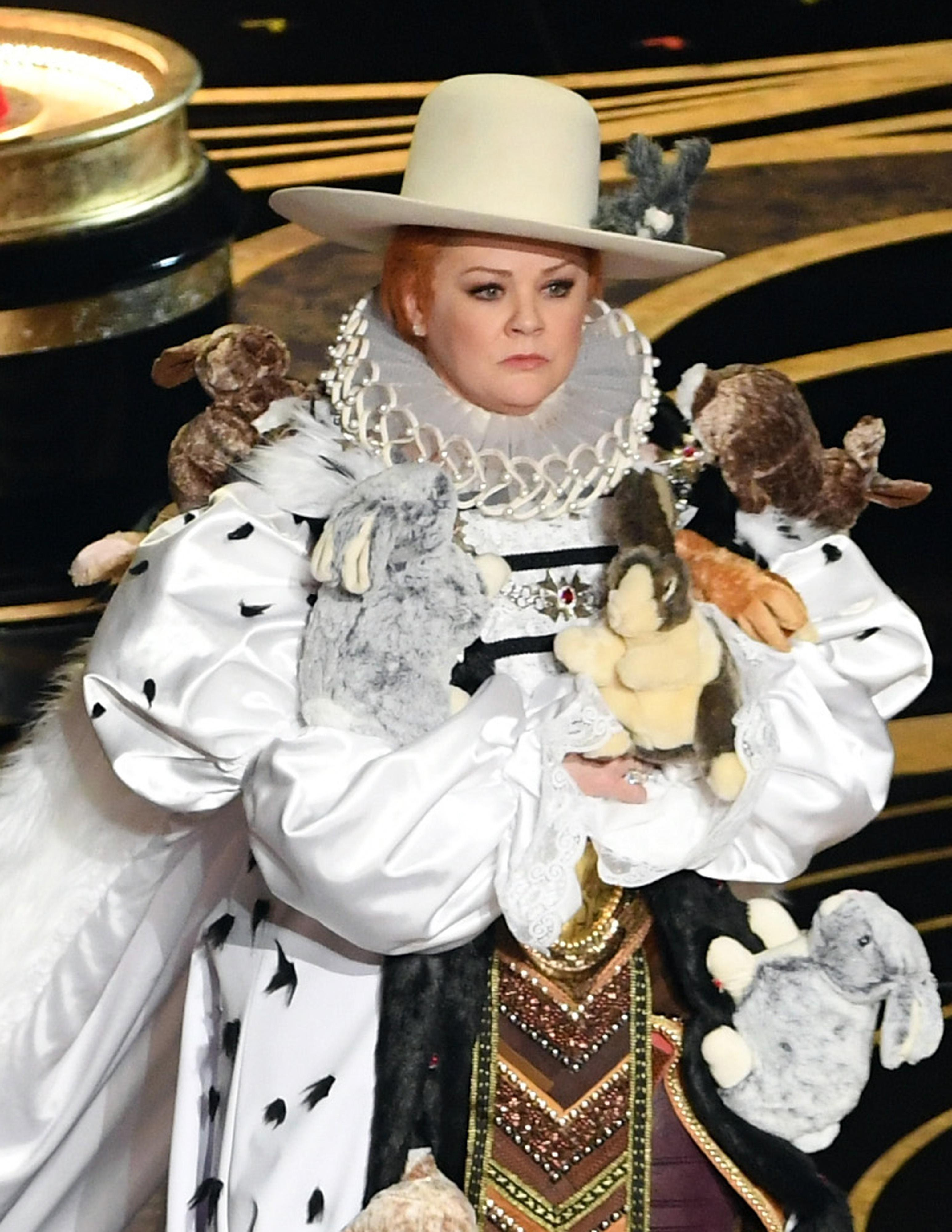 A close-up of Melissa McCarthy in costume. Her wide-brimmed hat has a stuffed rabbit on it.