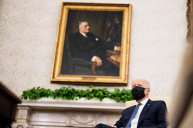 Joe Biden sits underneath a portrait of former President Franklin D. Roosevelt in the Oval Office.