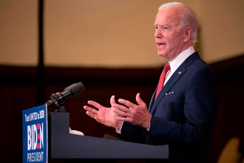 Biden, seen from the side, gestures with both hands while speaking from a lectern decorated with a red, white, and blue Biden for President sign.