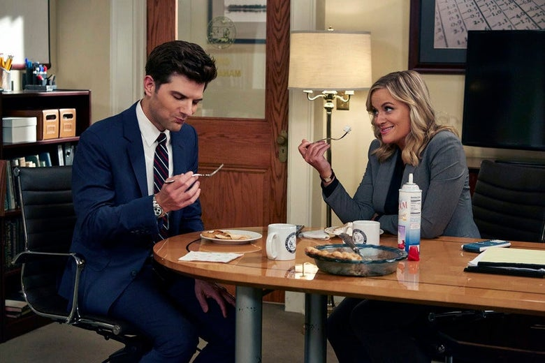 Adam Scott and Amy Poehler as Ben Wyatt and Leslie Knope, respectively, sit at a table and eat food.