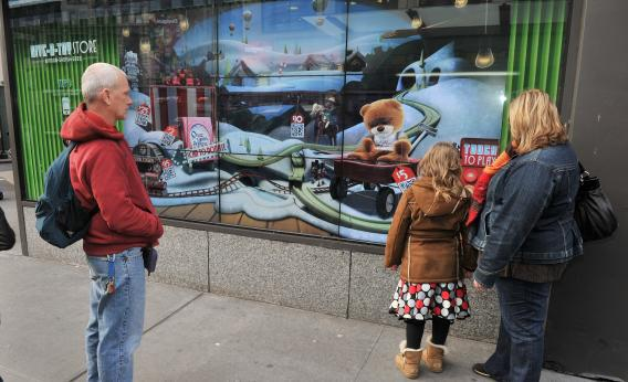 "EBay's new ""shoppable storefronts"" will let customers buy items on a touchscreen display on the front windows of vacant storefronts. Pictured above is a 2011 eBay initiative called the ""Give-a-Toy Store,"" which let shoppers in New York City's Herald Square donate to Toys for Tots from their mobile devices using QR codes."