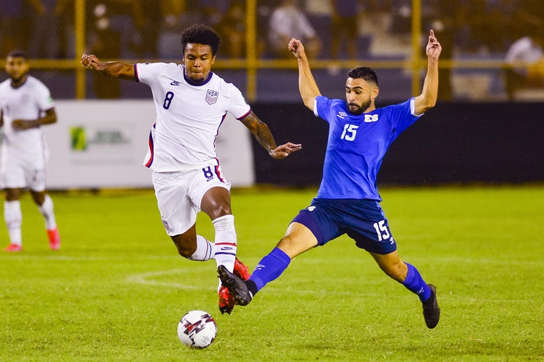 McKennie and Roldan fight for the ball, Roldan's legs outstretched and arms up, McKennie running straight at it with arms out